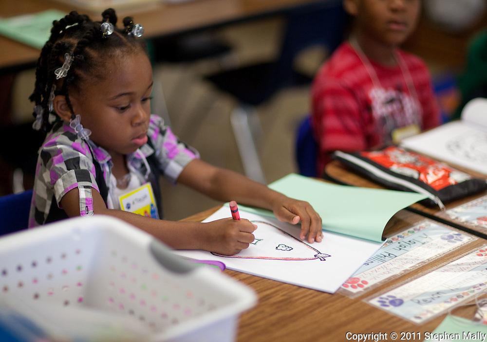 A'Tayjah Phillips, 5, kindergarten, of Cedar Rapids, works on coloring on the first day of school at Polk Elementary School, 1500 B Avenue NE, in Cedar Rapids on Thursday morning, July 21, 2011.