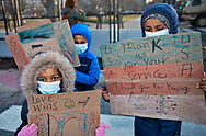 Children showing support for the millitary outside of the metal gate surrounding the US Captiol  in Washington D.C, before Biden's inuguration.