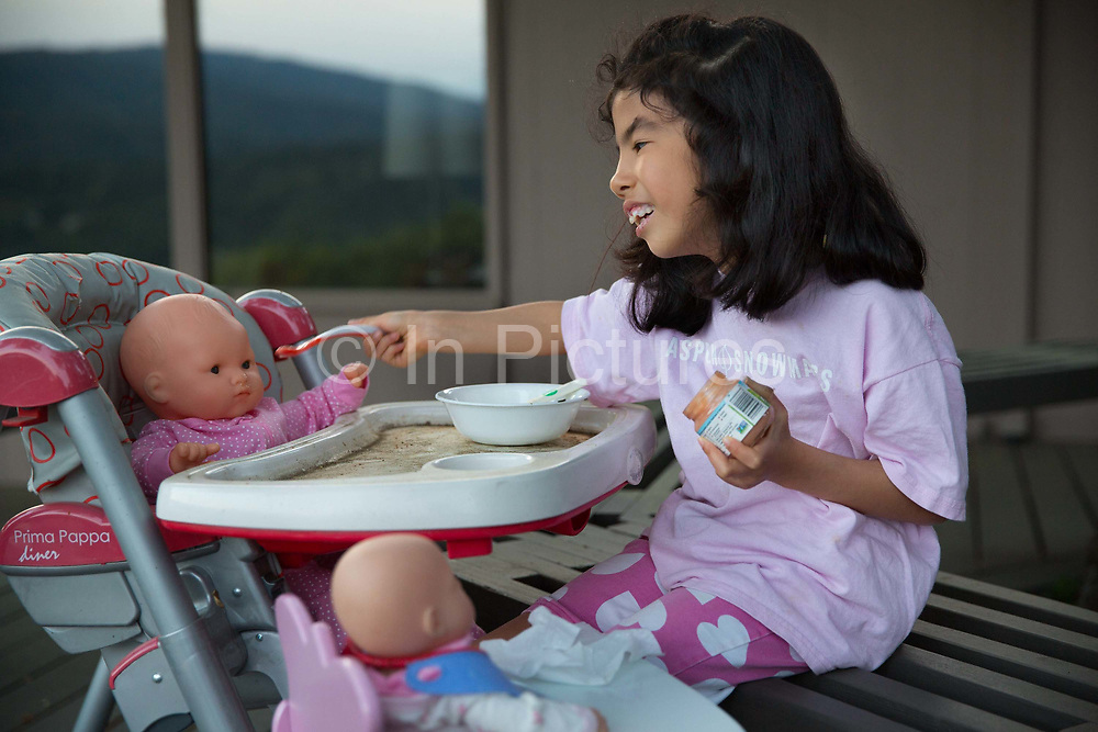 Young girl feeding her dolls in the Portola valley, California