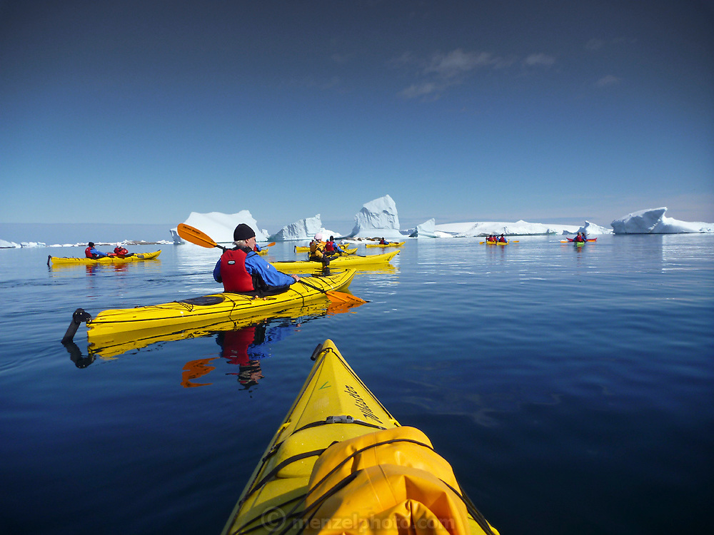 Kayaking off Petermann Island, home to the southernmost breeding colony of gentoo penguins, located below the Lemaire channel, near the Antarctic peninsula.