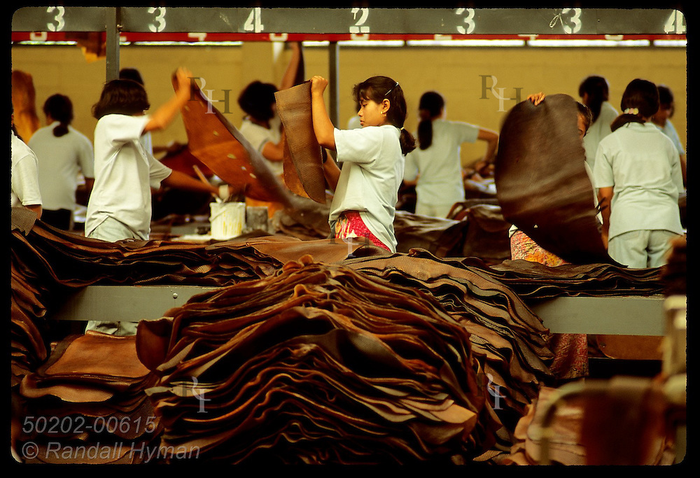 Women inspect rubber mats to cut out impurities before export from United Krabi Rubber Company Thailand