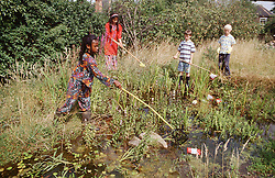 Multiracial group of young children removing rubbish from pond,