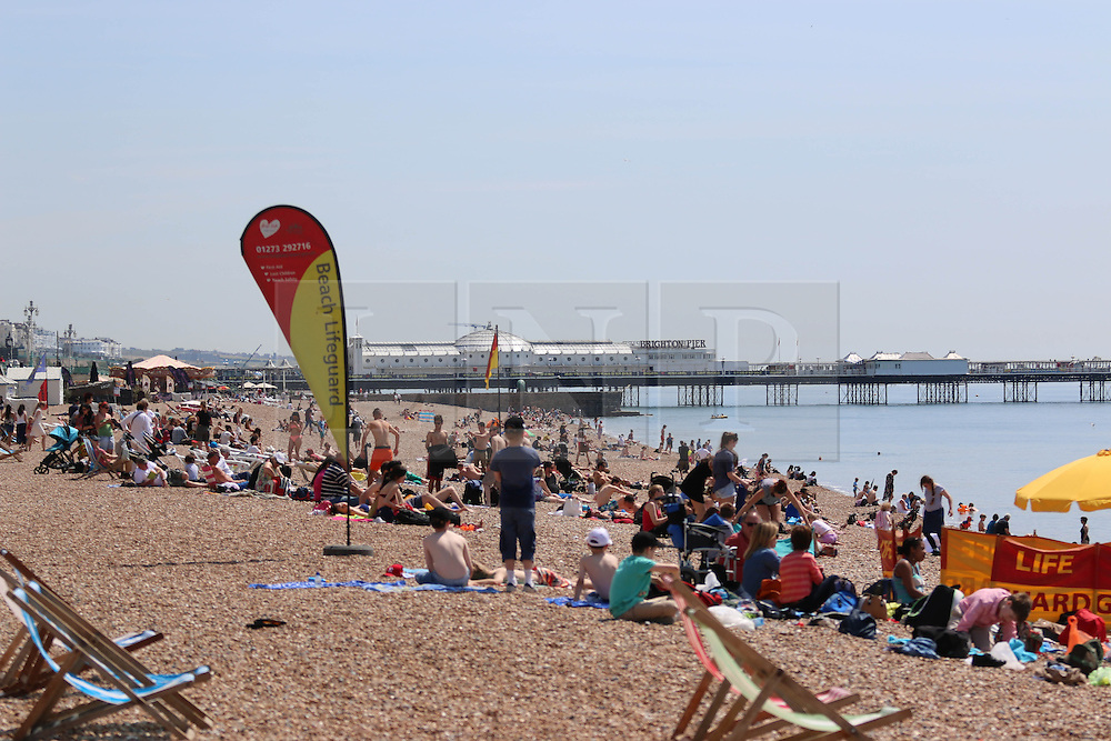 © Licensed to London News Pictures. 13/06/2014. Brighton, UK.  Today, Friday 13th June is expected to be the hottest day of the year so far with temperatures hitting nearly 30C at some locations. Brighton beach is slowly filling up with sunbathers and people wanting to relax by the beach. Photo credit : Hugo Michiels/LNP