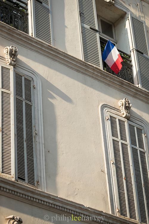 French flag hanging from window of old ornamental tenement house, Cannes, France