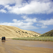 A vehicle heads towards 90-Mile Beach past sand dunes in Northland. Ninety Mile Beach is a beach located on the western coast of the far north of the North Island of New Zealand. It stretches from just west of Kaitaia towards Cape Reinga along the Aupouri Peninsula. Northland, New Zealand, 21st November 2010 Photo Tim Clayton