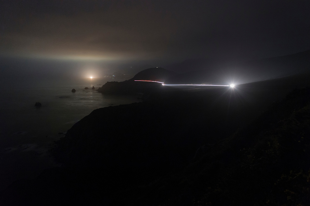 A single car illuminates Highway 1 along the cliffs of Big Sur. As seen from Hurricane Point. California.