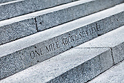 """SHOT 8/13/09 1:59:57 PM - The words """"One mile above sea level"""" mark the spot orginally thought to be 5,280 feet (or one mile) above sea level on the steps of the Colorado State Capitol. The official elevation of Denver is measured outside the west entrance to the building, where the fifteenth step is engraved with the words """"One Mile Above Sea Level."""" From this step, around dusk, a magnificent view of the sun setting behind the Rocky Mountains can be taken-in at 5,280 feet (1,609 m). A second mile high marker was set in the 18th step in 1969 when Colorado State University students resurveyed the elevation. Finally, in 2003, an even more accurate measurement was made with modern means and the 13th step was identified as being one mile (1.6 km) high where a 3rd marker was installed. Colfax Avenue is the main street that runs east and west through the Denver-Aurora metropolitan area in Colorado. As U.S. Highway 40, it was one of two principal highways serving Denver before the Interstate Highway System was constructed. In the local street system, it lies 15 blocks north of the zero point (Ellsworth Avenue, one block south of 1st Avenue). For that reason it would normally be known as """"15th Avenue"""" but the street was named for the 19th-century politician Schuyler Colfax. On the east it passes through the city of Aurora, then Denver, and on the west, through Lakewood and the southern part of Golden. Colloquially, the arterial is referred to simply as """"Colfax"""", a name that has become associated with prostitution, crime, and a dense concentration of liquor stores and inexpensive bars. Playboy magazine once called Colfax """"the longest, wickedest street in America."""" However, such activities are actually isolated to short stretches of the 26-mile (42 km) length of the street. Periodically, Colfax undergoes redevelopment by the municipalities along its course that bring in new housing, trendy businesses and restaurants. Some say that these new developments detract from the chara"""