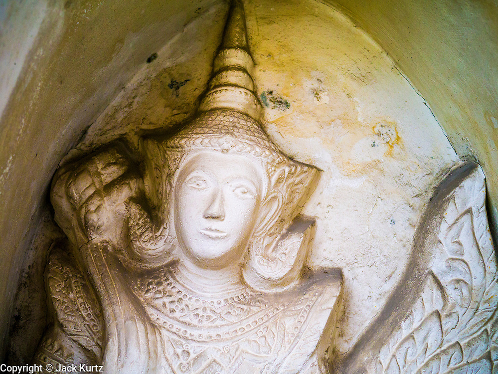 """17 MAY 2013 - BANGKOK, THAILAND: A figure from the Ramakien (Thai version of the Ramayana) in a niche at Wat Arun.  Wat Arun is a Buddhist temple (wat) in the Bangkok Yai district of Bangkok, Thailand, on the west bank of the Chao Phraya River. The full name of the temple is Wat Arunratchawararam Ratchaworamahavihara. The outstanding feature of Wat Arun is its central prang (Khmer-style tower). It may be named """"Temple of the Dawn"""" because the first light of morning reflects off the surface of the temple with a pearly iridescence. Steep steps lead to the two terraces. The height is reported by different sources as between 66,80 m and 86 m. The corners are surrounded by 4 smaller satellite prangs. The prangs are decorated by seashells and bits of porcelain which had previously been used as ballast by boats coming to Bangkok from China. The central prang is topped with a seven-pronged trident, referred to by many sources as the """"trident of Shiva"""". Around the base of the prangs are various figures of ancient Chinese soldiers and animals. Over the second terrace are four statues of the Hindu god Indra riding on Erawan. The temple was built in the days of Thailand's ancient capital of Ayutthaya and originally known as Wat Makok (The Olive Temple). In the ensuing era when Thonburi was capital, King Taksin changed the name to Wat Chaeng. The later King Rama II. changed the name to Wat Arunratchatharam. He restored the temple and enlarged the central prang. The work was finished by King Rama III. King Rama IV gave the temple the present name Wat Arunratchawararam. As a sign of changing times, Wat Arun officially ordained its first westerner, an American, in 2005. The central prang symbolizes Mount Meru of the Indian cosmology. The satellite prangs are devoted to the wind god Phra Phai.     PHOTO BY JACK KURTZ"""