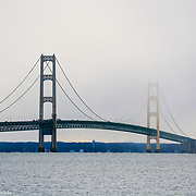 Mackinac Bridge One Tower Highlighted By Sunlight Shrouded In Clouds, The Other Darkened By Cloud Cover