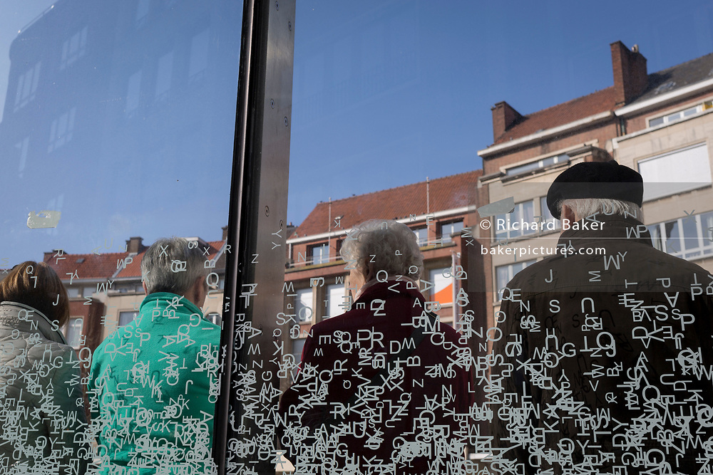 Elderly townspeople sitting against a background of alphabet letters on a bus shelter screen. on 24th March 2017, in Leuven, Belgium.