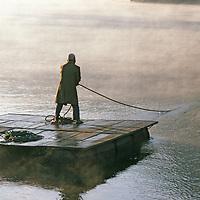 Pokhara, Nepal.Villager on raft crosses Lake Phewa Tal.