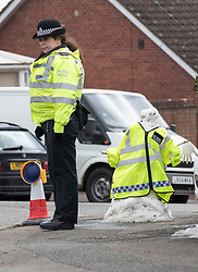© Licensed to London News Pictures. 20/03/2018. Salisbury, UK. A police officer from from Wales stands on duty next to the remains of a melting snowman wearing a high visibility police tabard on the road leading to the house of Sergei Skripal. Former Russian spy Sergei Skripal, his daughter Yulia are still critically ill after being poisoned with nerve agent. The couple where found unconscious on bench in Salisbury shopping centre. Authorities continue to investigate. Photo credit: Peter Macdiarmid/LNP