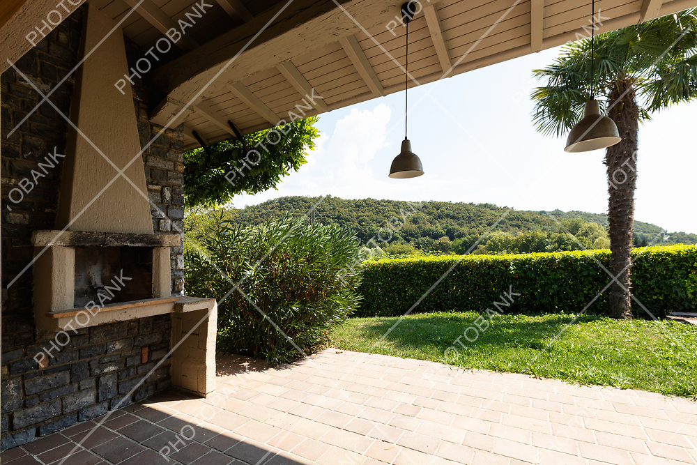 Patio with fireplace of a modern villa surrounded by green nature