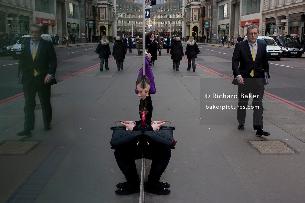 Symmetrical reflection of street woman, waiting for City of London bus.
