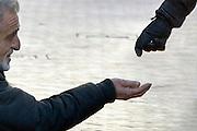 Nederland, Nijmegen, 19-1-2013Een bedelaar zit op zijn knieen en houdt zijn hand omhoog waar voorbijgangers een aalmoes, geld in kan stoppen. een jonge vrouw geeft hem wat muntgeld.De man komt uit Oost-Europa. Beeld is uitsnede uit origineel en bij de arm rechtsboven is een rood vlakje weggehaald.. Foto: Flip Franssen/Hollandse Hoogte