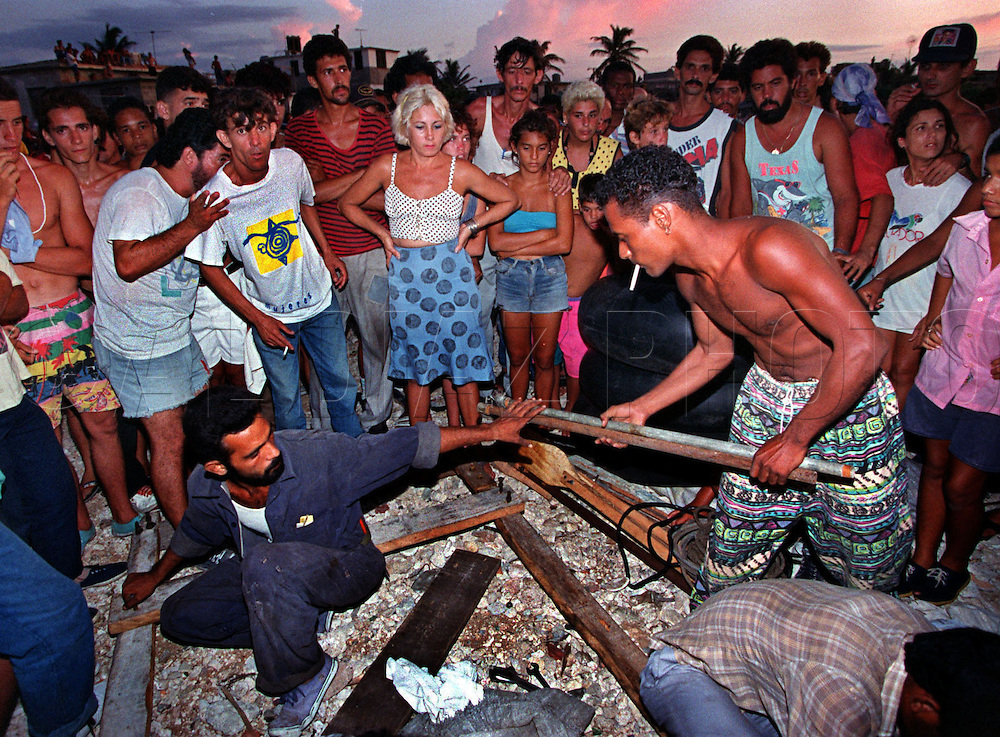 8/1994-Al Diaz/Miami Herald--Armando Alarcon Ramirez, holding salvaged material, at right, helps build his homemade raft before his departure from Cojimar, Cuba. The Cuban government offered very little resistance to the exodus. At one point, Cuban president Fidel Castro went on television and invited Americans to send boats to pick up refugees. He even offered to sell fuel to boaters to return to the United States, but many emigrants ended up making their own rafts.<br /> <br /> Between August 5 and September 13, 1994, more that 37,000 Cubans rode the Gulf Stream on a desperate journey to a new life in the United States. No corner of Cuba was untouched by the exodus.: Havana, Oriente, Matanzas. Out on the water, the rafters were subjected to pounding heat, 12-foot waves, and sharks. Most of these photographs in this gallery were taken during August 1994 in Cojimar, on the east side of Havana.