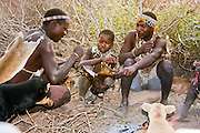 Hadzabe men around the camp filre cooking squirrel that they had hunted. Photographed in Tanzania, Lake Eyasi