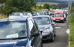 © Licensed to London News Pictures. 30/08/2020. City, UK. Cars parked by partygoers line the pavements in the village of Banwen in South Wales, during an illegal rave. The event, which was held in forestry above the village was attended by an estimated 3000 people from all over the UK. The government recently strengthened the laws to fine organisers of the illegal parties £10,000. Photo credit: Robert Melen/LNP