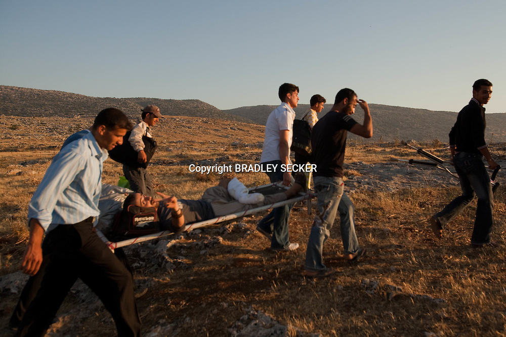 Syrian refugees carry an injured man towards the Turkish border, where they hope he will receive medical attention. Idlib province, Syria. 13/06/2012 Bradley Secker for USA Today
