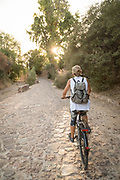 Rear view of woman cycling along street at sunset, Kambos, Chios, Greece