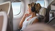 photographie d'une jeune femme en classe business pendant son vol dans un avion réalisée pour la photothèque Aircalin.