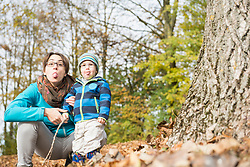 Portrait of mother and son sticking out tongue by big tree trunk in autumn