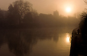 An angler fishing in the River Medway early in the morning, in front of a All Saints church in Maidstone. Kent, England, UK September 1991