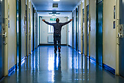 A prisoner walking with his arms out  down one of the corridors of the enhanced wing at <br /> HMP/YOI Portland, Dorset, United Kingdom.