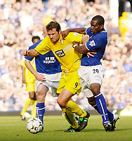 Photo. Jed Wee.<br /> Everton v Leeds United, FA Barclaycard Premiership, Goodison Park, Liverpool. 28/09/2003.<br /> Everton's Joseph Yobo (R) tries to get to grips with Leeds' Mark Viduka.