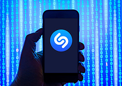 Person holding smart phone with Shazam online music recognition app logo displayed on the screen. EDITORIAL USE ONLY