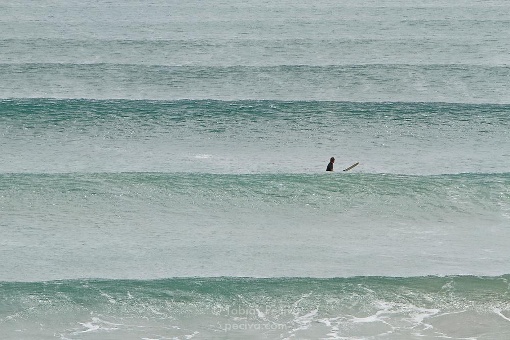 Lone surfer waiting for waves in Ngunguru Bay, near Pataua, Northland, New Zealand.