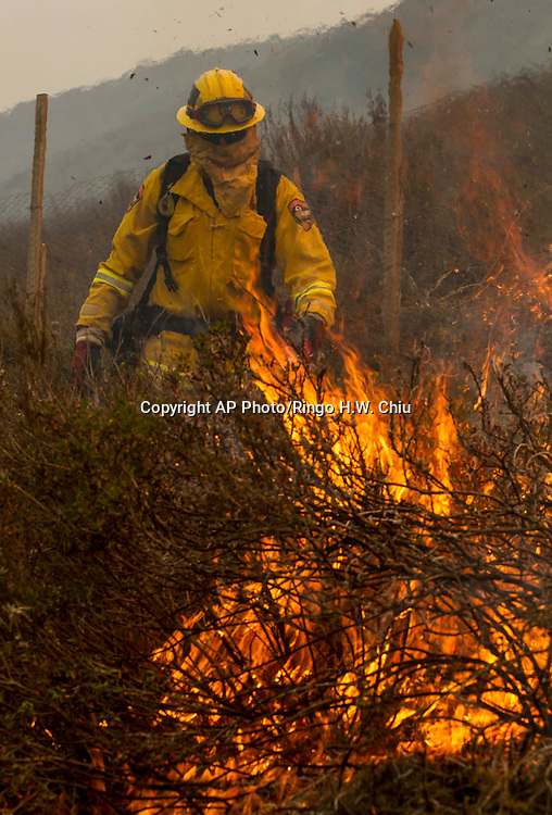 A firefighter sets a backfire to protest the farmland along a hillside in Point Mugu , Calif. Friday, May 3, 2013..(AP Photo/Ringo H.W. Chiu)