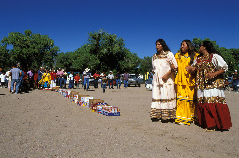 Apache Indians dance during a Sun Rise Dance, an Apache girl's first menstruation rite, on the San Carlos Apache Indian Reservation in Arizona, USA. The women are dressed in camp dresses. Behind the long row of cartons filled with snacks and drinks, symbolising a life without material want, the girl herself dances dressed in buckskin clothes. The ceremony is an enactment of the Apache creation myth and during the rites the girl 'becomes' Changing Woman, a mythical female figure, and comes into possession of her healing powers. The rites are also supposed to prepare the girl for adulthood and to give her a long and healthy life.