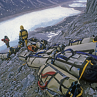 BAFFIN ISLAND, Nunavut, Canada. Rock climbers's haul bags on Great Sail Peak after month-long big wall expedition. Stewart Valley & frozen lake bkg.