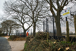 Great Missenden, UK. 9th April, 2021. HS2 security contractors guard a fenced area on Leather Lane where several hundred-year-old oak trees have been felled to enable the construction of a temporary access road and compound for the HS2 high-speed rail link. Following pressure from local residents, Buckinghamshire Council and the Chilterns Conservation Board, it appears that HS2 contractors have altered their plans in such a way as to preserve some of the trees lining the wildlife-rich ancient country lane.