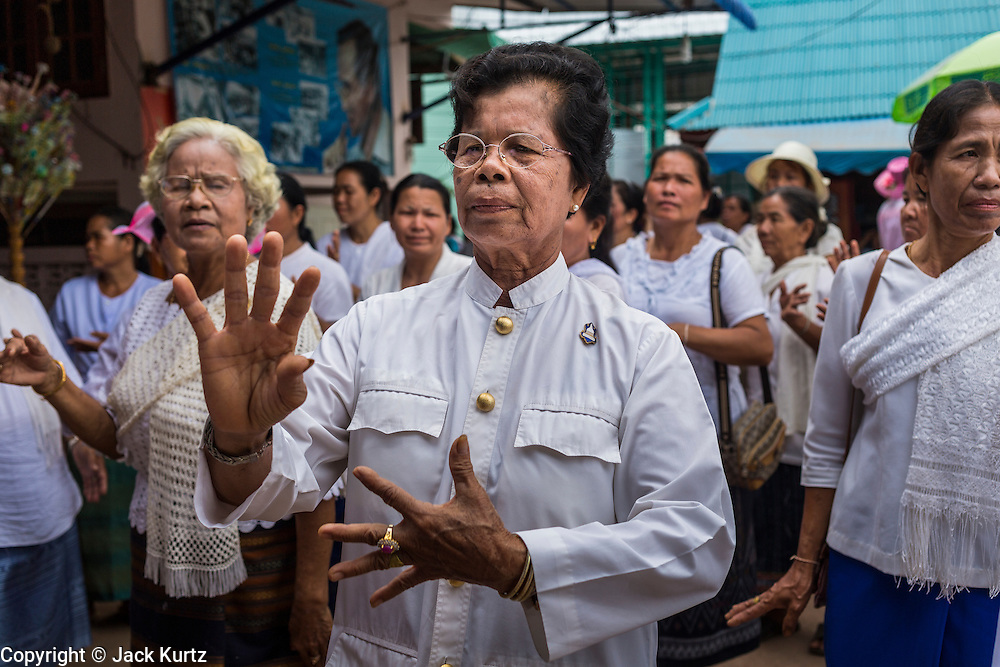29 JUNE 2014 - DAN SAI, LOEI, THAILAND: Women dance during a merit making procession on the last day of the Ghost Festival in Dan Sai.  Phi Ta Khon (also spelled Pee Ta Khon) is the Ghost Festival. Over three days, the town's residents invite protection from Phra U-pakut, the spirit that lives in the Mun River, which runs through Dan Sai. People in the town and surrounding villages wear costumes made of patchwork and ornate masks and are thought be ghosts who were awoken from the dead when Vessantra Jataka (one of the Buddhas) came out of the forest. On the last day of the festival people participate in merit making ceremonies at the Wat Ponchai in Dan Sai and lead processions through town soliciting donations for the temple.    PHOTO BY JACK KURTZ