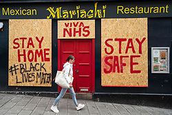 Edinburgh, Scotland, UK. 4 June 2020.  As Covid-19 lockdown relaxation continues in Scotland very few shops and businesses are open. Streets remain quiet and pubs and, with a few exceptions, bars and pubs are closed. Pictured; Black Lives Matter grafitti has been added to a boarded up restaurant in the Old Town. Iain Masterton/Alamy Live News