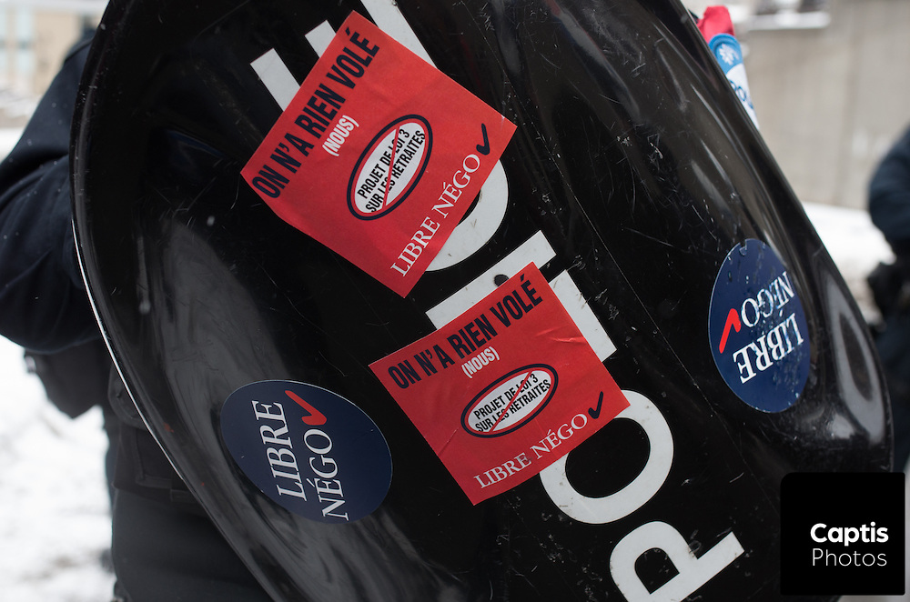 A Montreal police riot shield covered in stickers protesting Quebec's pension reform. March 15, 2015