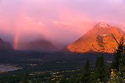 A rainbow forms just as the sun rises and hits a mountain in Glacier National Park, Montana.