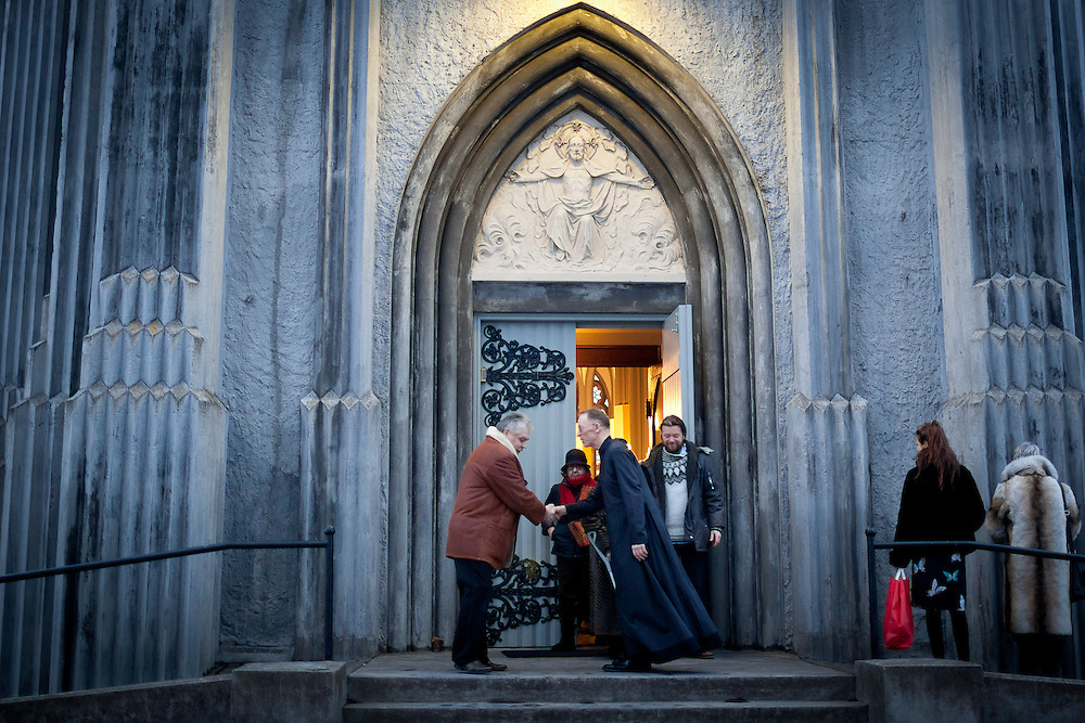 """The priest greets parishoners after Christmas Day mass at  Landakotskirkja (also named Basilika Krists konungs or in English """"The Basilica of Christ the King"""") in Reykjavik, Iceland on December 25, 2013. Only 3% of Icelanders are Catholic."""