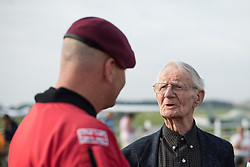 © Licensed to London News Pictures. 25/08/2016. <br /> <br /> Pictured: D-Day veteran Fred Glover meets a member of the Red Devils parachute display team prior to his parachute jump.<br /> <br /> Fred Glover and Ted Pieri, two D-Day veterans who are both 90 years old have parachuted into Sarum Airfield, Wiltshire on Thursday 25th August 2016, 72 years after D-Day having earlier in the month parachuted into Merville Battery in France.<br /> <br /> <br /> Photo credit should read Max Bryan/LNP