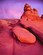 Sunset light illuminating virga over Entrada Sandstone slickrock, Arches National Park, Utah.