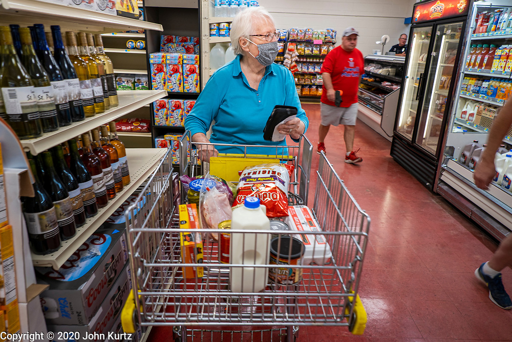 """08 JULY 2020 - JEWELL, IOWA: SHIRLEY ISEBRANDS, a lifelong resident of Jewell, IA, shops in the Jewell Market on the first day it was open. The only grocery store in Jewell, a small community in central Iowa, closed in 2019. It served four communities within a 20 mile radius of Jewell. Some of the town's residents created a cooperative to reopen the store. They sold shares to the co-op and  held fundraisers through the spring. Organizers raised about $225,000 and bought the store, which reopened July 8. Before the reopening, Jewell had been a """"food desert"""" for seven months. The USDA defines rural food deserts as having at least 500 people in a census tract living 10 miles from a large grocery store or supermarket. There is a convenience store in Jewell, but it sells mostly heavily processed, unhealthy snack foods that are high in fat, sugar, and salt.         PHOTO BY JACK KURTZ"""