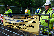 Balcombe, West Sussex. Site of Cuadrilla drilling. Demonstration against fracking 18.08.2013. At the entrance to the site a Gurkha security guard stands next to police, behind a banner saying Balcombe is 82%  against fracking and 100% against illegal action.