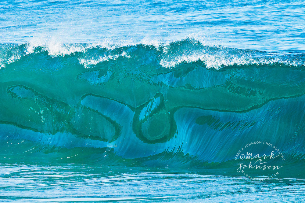 Light and reflections make the shape of a whale's tail in a breaking ocean wave off Kauai, Hawaii