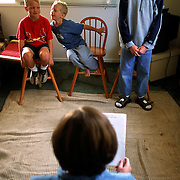 Jeanne has the boys recite poetry in the home's living room as part of Language Arts.