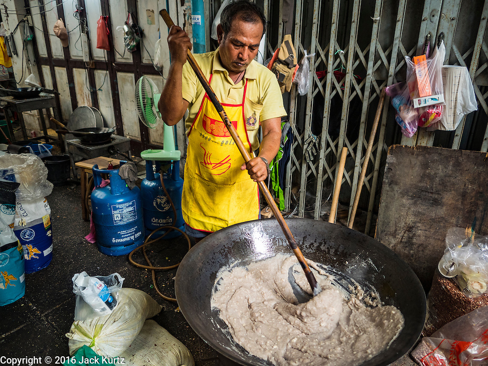 04 OCTOBER 2016 - BANGKOK, THAILAND:  A man makes Chinese peanut snacks at the Vegetarian Festival at the Chit Sia Ma Chinese shrine in Bangkok. The Vegetarian Festival is celebrated throughout Thailand. It is the Thai version of the The Nine Emperor Gods Festival, a nine-day Taoist celebration beginning on the eve of 9th lunar month of the Chinese calendar. During a period of nine days, those who are participating in the festival dress all in white and abstain from eating meat, poultry, seafood, and dairy products. Vendors and proprietors of restaurants indicate that vegetarian food is for sale by putting a yellow flag out with Thai characters for meatless written on it in red.    PHOTO BY JACK KURTZ