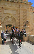 Tourists in horse and carriage at entrance gateway to medieval city of Mdina, Malta