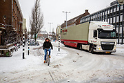In Utrecht manouvreren een fietser en vrachtwagen, op weg naar de supermarkt, door de sneeuw. Nederland geniet van de eerste sneeuw sinds lange tijd.<br /> <br /> In Utrecht a cyclists and a truck manouvre in the snow. People in the Netherlands enjoy the first snow since years.