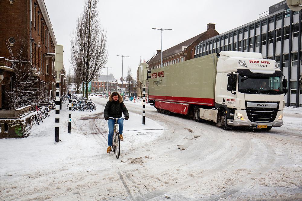 In Utrecht manouvreren een fietser en vrachtwagen, op weg naar de supermarkt, door de sneeuw. Nederland geniet van de eerste sneeuw sinds lange tijd.<br /> <br /> In Utrecht a cyclists and a truck manouvre in the snow. People in the Netherlands enjoy the first snow since years.